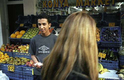 Dutch-Turkish teenager Hakan Dinc looks at a customer while he works at his uncle's grocery store in Amsterdam. .Dinc, 16, was born in the Netherlands. His grandparents from his father?s side came from Turkey in 1971, and his mother came in 1987. Dinc feels more Turkish than Dutch, most of his friends are Turkish and he wants to marry a Turkish girl. During his time off he works in his uncle?s grocery store. Later, he wants to have his own shop. Dinc is following a Commerce course at a vocational school in Amsterdam. .Dinc likes music, pool and chilling out. He has a fourteen-year-old sister and a brother aged ten months. .Picture shot in Amsterdam in 2004 by Justin Jin. .