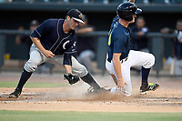 Left fielder Ian Strom (40) of the Columbia Fireflies is safe at home on a wild pitch as pitcher Nick Green applies the tag too late in a game against the Charleston RiverDogs on Monday, August 7, 2017, at Spirit Communications Park in Columbia, South Carolina. Columbia won, 6-4. (Tom Priddy/Four Seam Images)