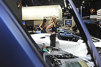 Car girls pose beside a convertible next to the 2009 Lamborghini Murcielago at the Detroit Auto Show in Detroit, Michigan on January 11, 2009.