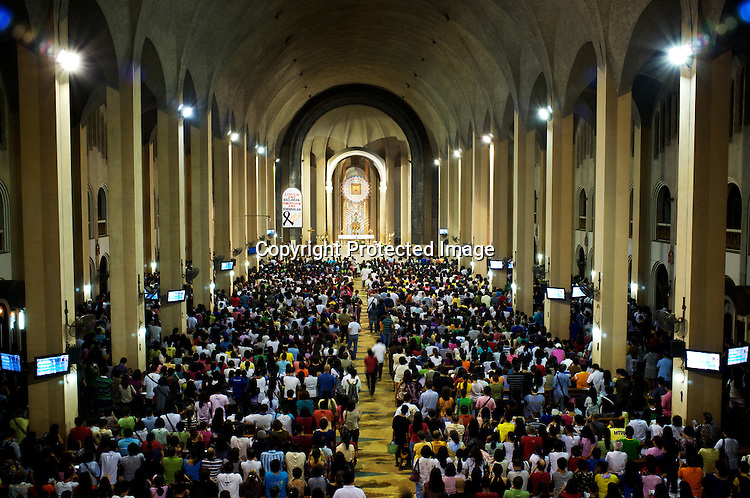 """Worshippers attend the evening mass on wednesday evening at the Redemptorist Church in Baclaran in Manila, Philippines. The Baclaran church is said to be the most attended church in Asia drawing up to 100,000 worshippers """" in Manila, Philippines. Photo: Sanjit Das"""