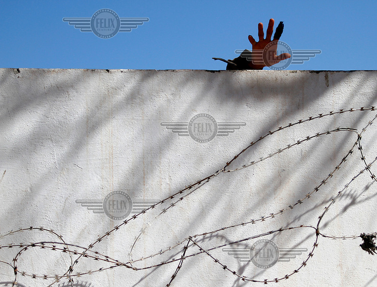 A man strech a hand over the border wall. Tens of thousands of people, mainly Egyptian workers, fled unrest in Libya and crossed the border into Tunisia. Some slept in the open for several days before being processed.  At the same time forces loyal to Col. Gaddafi fought opposition forces in various parts of the country.