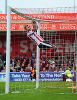 Lincoln City's Matt Rhead hangs on the crossbar after Exeter City's Christy Pym had beaten him to a high ball<br /> <br /> Photographer Chris Vaughan/CameraSport<br /> <br /> The EFL Sky Bet League Two Play Off First Leg - Lincoln City v Exeter City - Saturday 12th May 2018 - Sincil Bank - Lincoln<br /> <br /> World Copyright &copy; 2018 CameraSport. All rights reserved. 43 Linden Ave. Countesthorpe. Leicester. England. LE8 5PG - Tel: +44 (0) 116 277 4147 - admin@camerasport.com - www.camerasport.com
