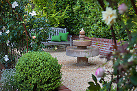 Stone, tiered fountain on secret garden patio with bench on pea gravel surface
