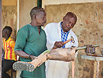 Jany Mahmed and Lawrence Angatai (right) adjust a new leg in the prosthetics department of the Mother of Mercy Hospital in Gidel, a village in the Nuba Mountains of Sudan. The area is controlled by the Sudan People's Liberation Movement-North, and frequently attacked by the military of Sudan. The Catholic hospital is the only referral hospital in the war-torn area, and has dealt with many amputations of people injured by bombs, artillery, and gunshot wounds.
