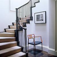 A designer armchair occupies a space on an upper floor landing
