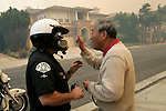 Oct 13, 2008 - Porter Ranch, California, USA - LAPD officer Troy Williams talks with a homeowner in Porter Ranch as mandatory evacuations are ordered while out of control wildfire burns around the neighborhood   Monday October 13, 2008 in the San Fernando Valley.(Credit Image: © Jonathan Alcorn/ZUMA Press)