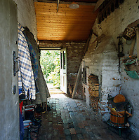 Coats, boots, logs and tools are stored in this cobbled passage which doubles as a boot room