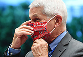Director of the National Institute for Allergy and Infectious Diseases Dr. Anthony Fauci puts on a Washington Nationals face mask when he arrives to testify before the House Committee on Energy and Commerce on the Trump Administration's Response to the COVID-19 Pandemic, on Capitol Hill in Washington, DC on Tuesday, June 23, 2020.    <br /> Credit: Kevin Dietsch / Pool via CNP