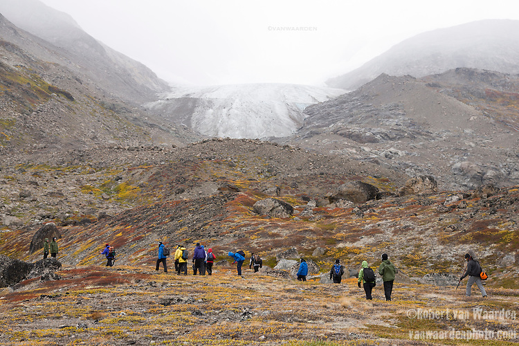 Students from the Cape Farewell Youth Expedition walk through the Greenland landscape. In the background a glacier that is receding dramatically from climate change.
