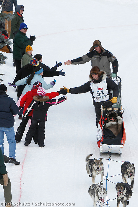 Spectators cheer on Pete Kaiser on the bike trail near the Native Hospital in mid-town Anchorage during the ceremonial start of the 2011 Iditarod