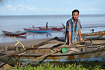 Ahmad Syarit stands by his small fishing boat on the beach near Olora, a village on the Indonesian island of Nias. Syarif survived a giant March 2005 earthquake on Nias, yet lost much of his fishing equipment. Church World Service, a member of the ACT Alliance, provided new nets and boats for the fishers of Olora, allowing them to restart their lives. Yet fish have grown scarce in recent years, while fuel prices have risen, making it harder for fishers to earn a living. Climate change has also made it more difficult to predict fish movements, and changing weather patterns can surprise the fishermen at sea.