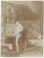 11a.<br /> <br /> 4 3/8  x  3 5/16  [sepia]<br /> <br /> S. H. Crone, full posterior figure, three-quarter turned with face in profile, wearing shirt and sash in his studio with high ceiling; framed still life with the familiar compote and another still life behind,  at left; larger unframed still life painting, small portrait of man with beard (perhaps, Crone), at right; other painting along floor; walls draped to ceiling with cloths and curling pin-ups.<br /> This is probably at Klenzestrasse.