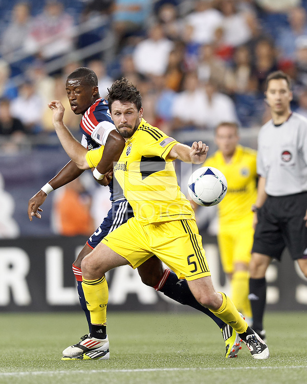 Columbus Crew defender Danny O'Rourke (5) attempts to control the ball as New England Revolution forward Dimitry Imbongo (92) defends. Note: Referee is looking at backs of players. In a Major League Soccer (MLS) match, the New England Revolution defeated Columbus Crew, 2-0, at Gillette Stadium on September 5, 2012.