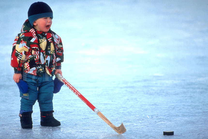 Little boy bundled up standing on ice holding a hockey stick and crying.