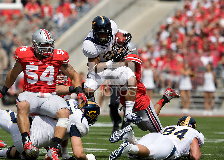 Isi Sofele of California leaps over Ohio State defenders during the game at Ohio Stadium in Columbus, Ohio on September 15th, 2012.   Ohio State Buckeyes defeated California Bears, 35-28.