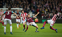 Mark Noble of West Ham United between Mame Biram Diouf (18) & Joe Allen of Stoke City during the Premier League match between West Ham United and Stoke City at the Olympic Park, London, England on 16 April 2018. Photo by Andy Rowland.