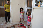 Young Iraqi Christian refugee from Mosul, Dilar Minowar Salim, 9 (C), is seen with members of her extended family at the partially finished house they share in Hamdaniyah, Iraq.