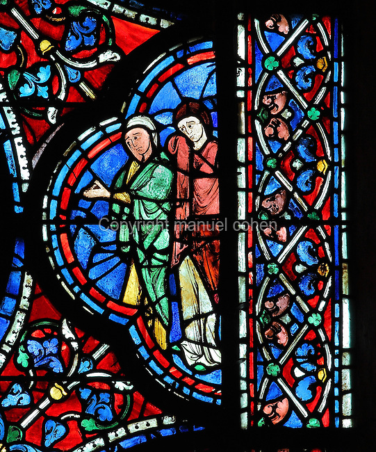 A female saint and a woman to the right of the scene of the apostles at the deathbed of Mary, The Death of the Virgin, from the Glorification of the Virgin stained glass window, in the nave of Chartres Cathedral, Eure-et-Loir, France. This window depicts the end of the Virgin's life on earth, her dormition and assumption, as told in the apocryphal text the Golden Legend of 1260. Chartres cathedral was built 1194-1250 and is a fine example of Gothic architecture. Most of its windows date from 1205-40 although a few earlier 12th century examples are also intact. It was declared a UNESCO World Heritage Site in 1979. Picture by Manuel Cohen