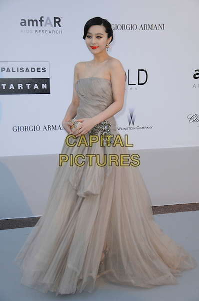 FAN BINGBING.arrivals at amfAR's Cinema Against AIDS 2010 benefit gala at the Hotel du Cap, Antibes, Cannes, France during the Cannes Film Festival.20th May 2010.amfAR full length long maxi dress strapless beige gown ballgown cream clutch bag  tulle .CAP/CAS.©Bob Cass/Capital Pictures.