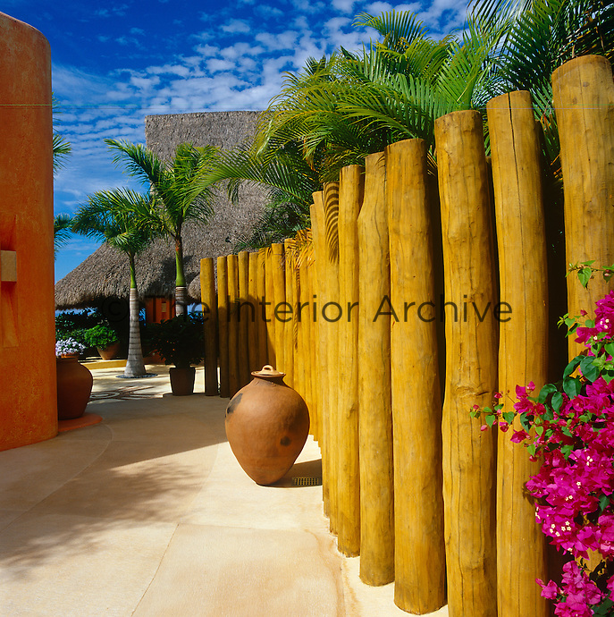 The entrance to the property is bordered by a fence of stained tree trunks
