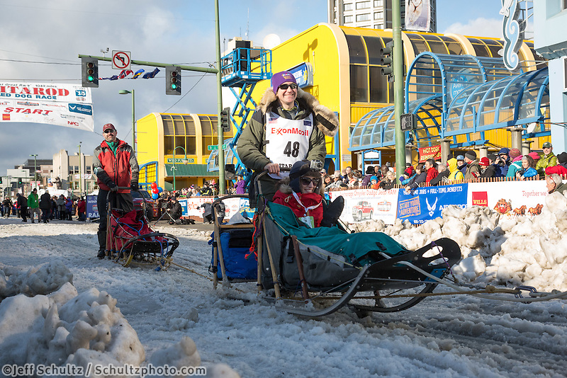 Bryan Bearss and team leave the ceremonial start line with an Iditarider at 4th Avenue and D street in downtown Anchorage, Alaska during the 2015 Iditarod race. Photo by Jim Kohl/IditarodPhotos.com