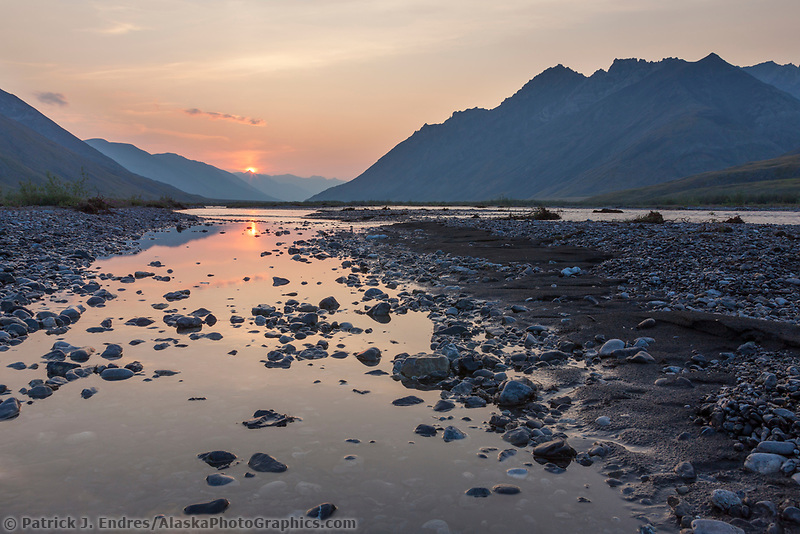 Midnight sun over the Marsh Fork of the Canning river, which comprises the western border of the Arctic National Wildlife Refuge in the Brooks Range mountains, Alaska.