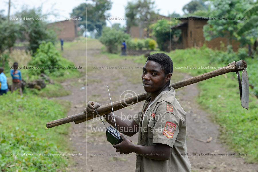 RUANDA, Ruhengeri, Virunga Mountains, farmer with hoe and chinese X-Bass  radio / Virunga Berg- und Vulkanlandschaft, kleinparzellige Landwirtschaft, Kleinbauer mit chinesischem X-Bass radio und hacke