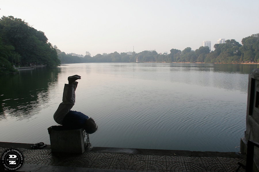 A man stretches while exercising next to Hoan Kiem Lake in Hanoi, Vietnam at sunrise.  The lake is a popular place in the morning for residents of the old quarter of Hanoi to jog,  practice t'ai chi, or play badminton.  Photograph by Douglas ZImmerman