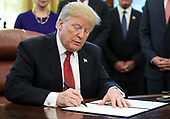 """United States President Donald J. Trump signs an Executive Order to strengthen the Trump Administration's """"Buy American"""" policy by encouraging recipients of Federal financial assistance for infrastructure to """"Buy American"""" in the Oval Office of the White House on January 31, 2019 in Washington, DC. <br /> Credit: Oliver Contreras / Pool via CNP"""