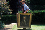 Newnham, Northamptonshire, England. A country house auction is conducted by the London auctioneers Christies at Newnham Hall. A  porter carries two period oil painting  from the main house to the marquee that has been set up in the grounds and is where the auction takes place.