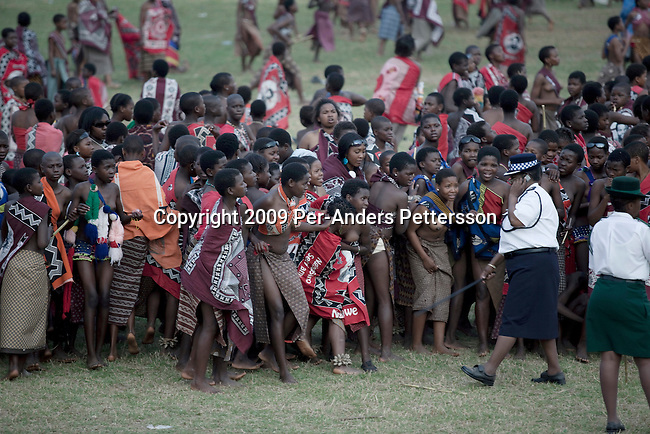 LUDZIDZINI, SWAZILAND - AUGUST 31: Police control young girls at a traditional Reed dance ceremony at the stadium at the Royal Palace on August 31, 2009, in Ludzidzini, Swaziland. About 80.000 virgins from all over the country attended this yearly event, the biggest in Swazi culture. It was founded to celebrate the beauty of Swazi women and girls. King Mswati III, and absolute monarch, was born in 1968 and he has 14 wives and many children. The king danced with his men in front of the 80.000 girls. Many of the girls hope to get noticed by the king and to be chosen as a future wife, a ticket from poverty and into a life of privilege and luxury. The country is one of the poorest in the world and it is struggling with a high prevalence of HIV-Aids and severe poverty. (Photo by: Per-Anders Pettersson)...
