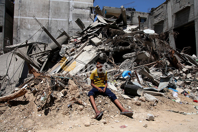 """A Palestinian boy sits on the debris of his family's house after it was hit by an Israeli military strike in Gaza city on August 10, 2014. A senior Hamas official said there was a """"weak"""" possibility that Gaza truce talks would succeed and that Palestinian negotiators could leave Cairo after a meeting with Egyptian mediators. Photo by Ezz Zanoun"""