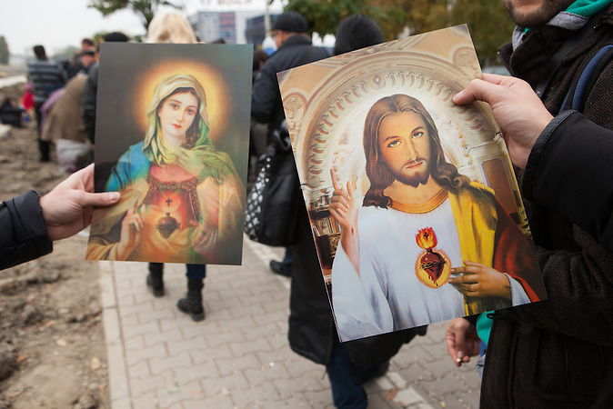 Pilgrims stand in queue to worship the relics of saint Parascheva in Iasi, showcase the religious souvenirs that they have bought from street sellers, October 12, 2013. The revenues from the pilgrimage of the Romanian Orthodox Church are estimated at couple of million euros.