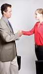 A businessman and businesswoman handshaking.  People are blurred