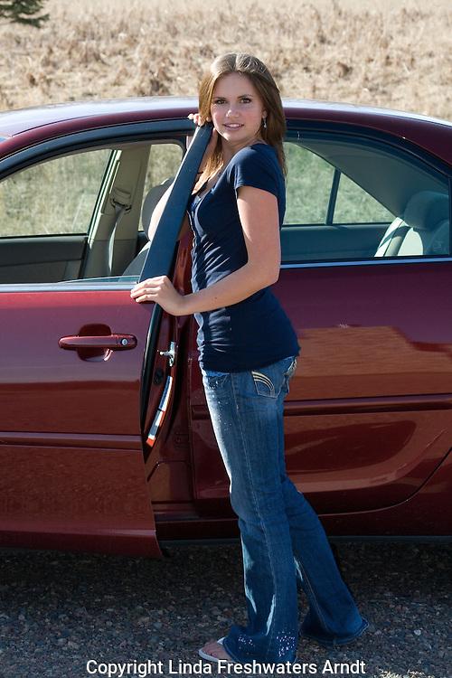 Teenager posing next to car