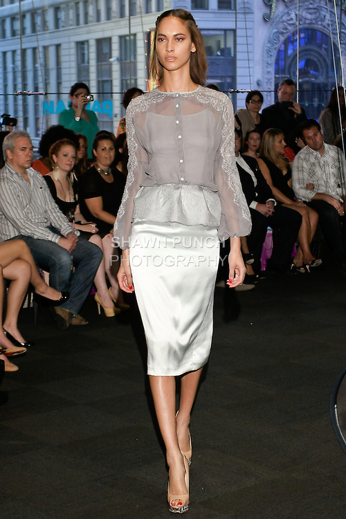 """Model walks runway in a white embroidered dot jacket dress, from the Yuna Yang Spring Summer 2013 """"Close your eyes and see the world"""" collection, at the NASDAQ Marketsite, during New York Fashion Week, on September 7, 2012."""
