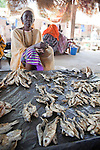 In Segou, Mali, a woman sells piles of fish in the market.