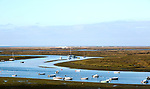 Coastal landscape of salt marsh with boats moored in meandering river drainage channels along the coastline off Faro, Algarve, Portugal