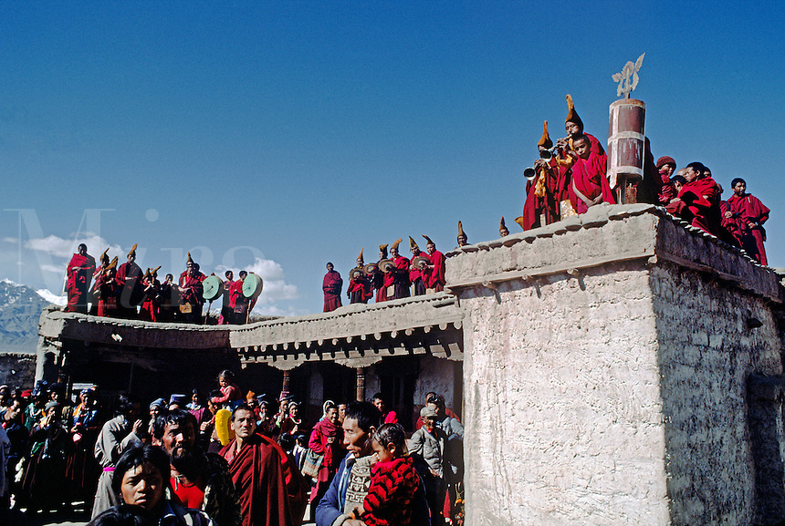 GELUGPA (yellow hat) MONKS PLAY MUSIC on a rooftop overlooking the TIKSE Monastery GOSTOR (mask dances) - LADAKH, INDIA..