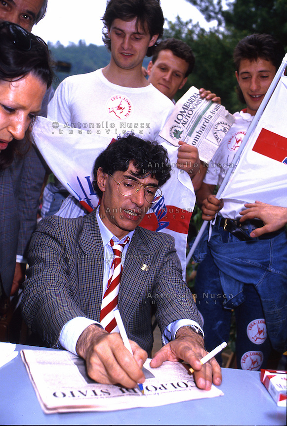 April 1994, Pontida Italy. Umberto Bossi, former minister in Berlusconi's cabinet, and founder of the right-wing, xenophobic Italian party Lega Nord, just resigned from his office as party secretary. This happens as consequence of a series of scandals linked to Bossi and other major figures of Lega Nord..Umberto Bossi signing autograph during the national rally of Lega Nord in Pontida.