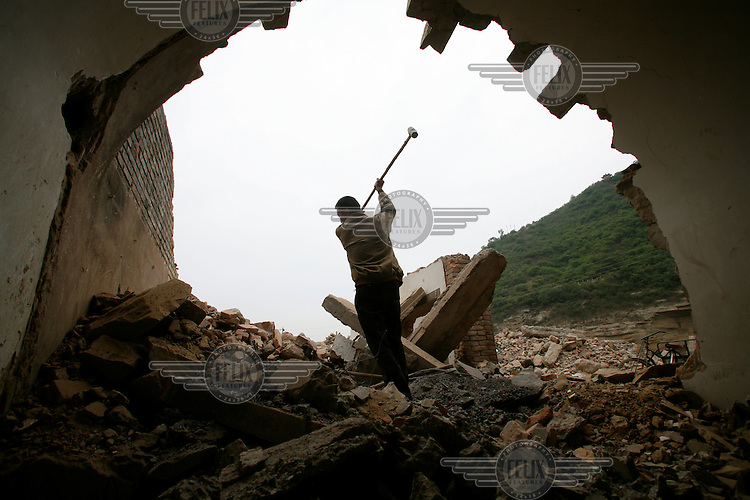 Villagers work to salvage bricks and metal for scrap at a site where traditional cave dwellings are being demolished and  new apartments being built near Yanan in rural Shaanxi Province.