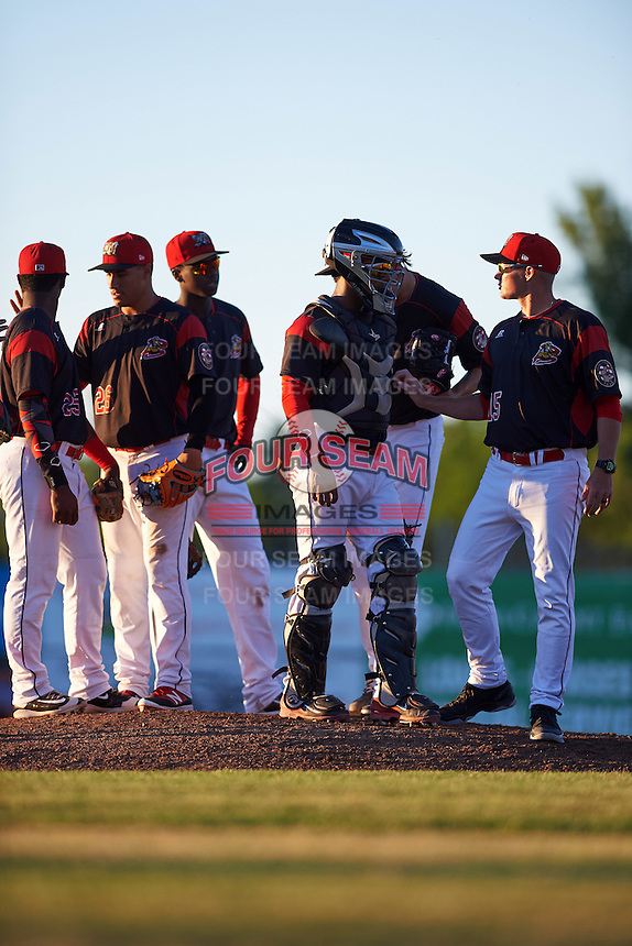 Batavia Muckdogs pitching coach Chad Rhoades (15) talks with pitcher Jordan Holloway (56) and catcher Pablo Garcia (7) with Samuel Castro (25), Rony Cabrera (26), and Javier Lopez (23) to the left during a game against the West Virginia Black Bears on June 30, 2016 at Dwyer Stadium in Batavia, New York.  Batavia defeated West Virginia 4-3.  (Mike Janes/Four Seam Images)