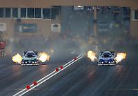 Jul. 18, 2014; Morrison, CO, USA; NHRA funny car driver John Force (left) races alongside Robert Hight during qualifying for the Mile High Nationals at Bandimere Speedway. Mandatory Credit: Mark J. Rebilas-