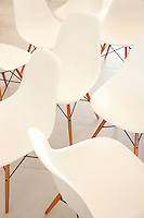 Grouped together in the dining room is a collection of white dining chairs by Charles Eames