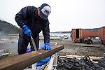 Fisherman Kenji Abe saws some wood to make a storage frame for his fellow fisherman in Kyubun, Ishinomak, Miyagi Prefecture, Japan on 29 Feb. 2012. .Photographer: Robert Gilhooly