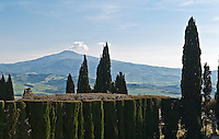 Cypress trees and a clipped yew hedge are silhouetted against Monte Amiata beyond the garden