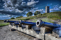 Old cannon at the Tønsberg citadel (Tunsbergshus) with castle rising in the background.
