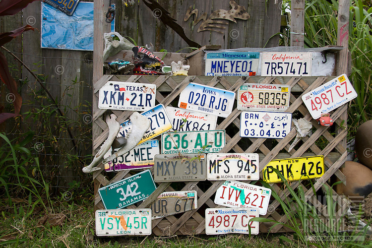 A collection of license plates cover the front of a fruit stand along the road to Hana, Maui.