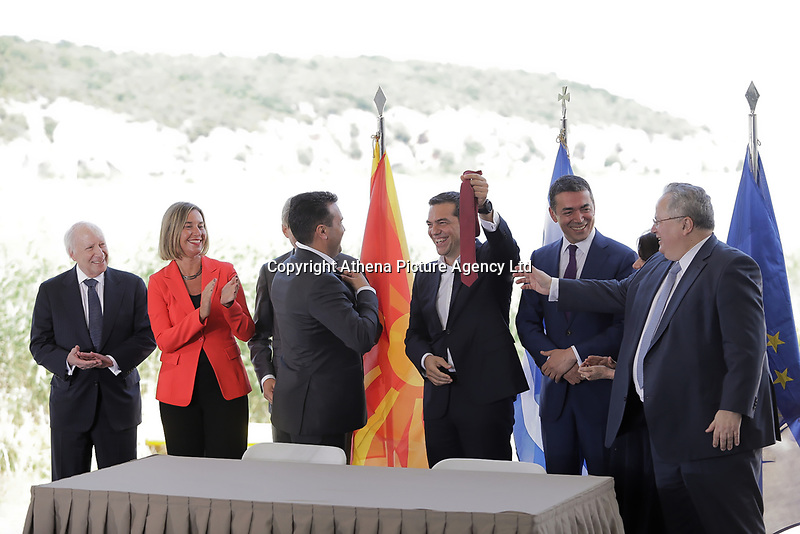 Pictured: Zoran Zaevat, Prime Minister for FYROM (C) jokes with Greek Prime Minister Alexis Tsipras who holds up his red tie at Prespa Lake in northern Greece. Sunday 17 June 2018<br /> Re: Greece and the Former Yugoslav Republic Of Macedonia (FYROM) have signed a deal that aims to settle a decades-long dispute over the country's name.<br /> Under the agreement, Greece's neighbour will be known as North Macedonia.<br /> Heated rows over Macedonia's name have been going on since the break-up of the former Yugoslavia, of which it was a part, and have held up Macedonia's entry to Nato and the EU.<br /> Greece has long argued that by using the name Macedonia, its neighbour was implying it had a claim on the northern Greek province also called Macedonia.<br /> The two countries' leaders, Mr Tsipras and his Macedonian counterpart Zoran Zaev announced the deal on Tuesday and have pressed ahead despite protests.<br /> The two countries' foreign ministers signed the deal on Lake Prespa on Greece's northern border on Sunday.<br /> The agreement still needs to be approved by both parliaments and by a referendum in Macedonia.