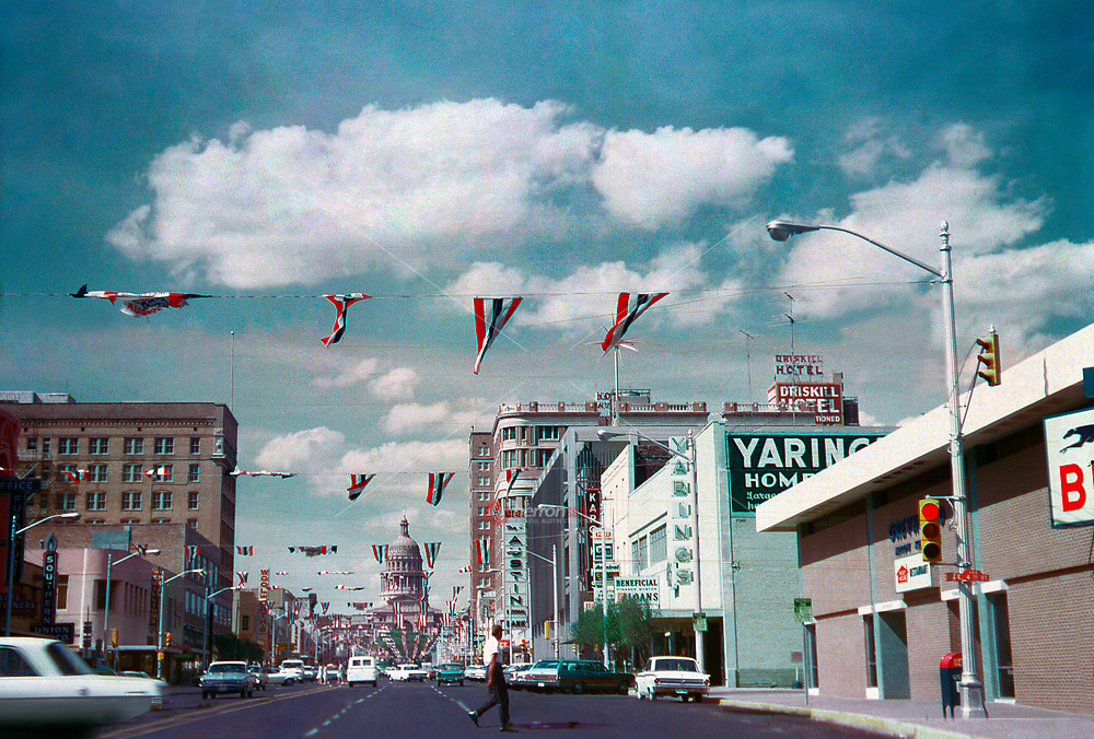 "A man crosses the street in this vintage 1960s view of 4th and Congress Avenue in downtown Austin with Texas State Capitol and festive red, white and blue streamers that say ""Welcome to Downtown Austin."" Notable landmarks include the Greyhound Bus Station, Driskill Hotel, Southern Union, Woolworths and the Austin National Bank."